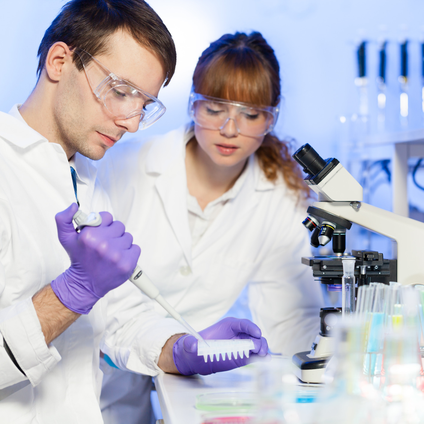 Laboratory researchers professionals pipetting into a well plate